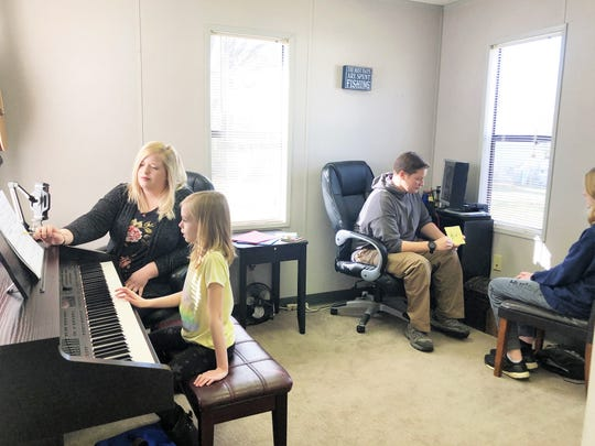 "Allison Combs teaches Lauren Wahl, while her brother, Mattthew teaches Lauren's brother Eric, music theory in their group lesson time at Allegro Knoxville Music Studio. ""Students can learn both piano and voice,"" said owner, Susan Rhea. ""We try to be flexible with parents and students, they may learn one instrument during the year and then do a totally different one in summer."""