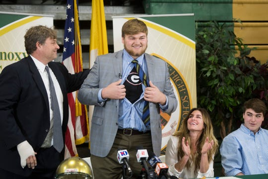 Cade Mays shows a Georgia T-shirt as he stands between his dad, Kevin, and mom, Melinda, during a signing day  ceremony at Knoxville Catholic High School in Knoxville, Tenn., Wednesday, Dec. 20, 2017. Kevin Mays is suing Georgia for an injury to his right pinkie finger.