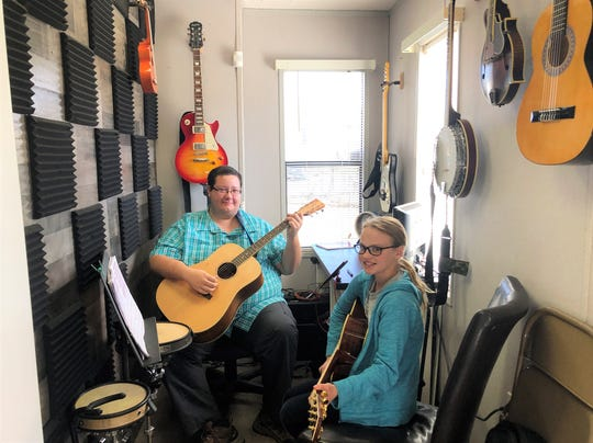Mark Rhea teaches Irelan Fender the acoustic guitar at Allegro Knoxville Music Studio.