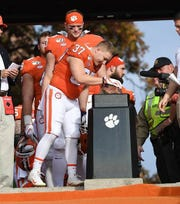 Clemson running back Tyler Traynham touches Howard's Rock as seniors come down during pregame ceremonies.