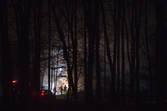 Backlit smoke through trees on the 3000 block of Sesame Drive in Marion Township is pierced by the sparks of something exploding during a house fire in the early hours of Wednesday, Jan. 8, 2020.