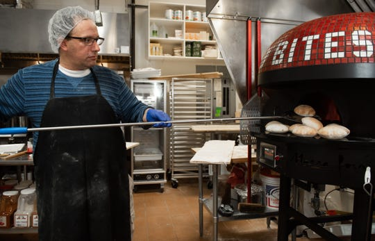 Pastry chef and baker Fadi Assaf pulls freshly-baked pita bread from the oven at Bread Bites in Okemos, Wednesday, Jan. 8., 2020.