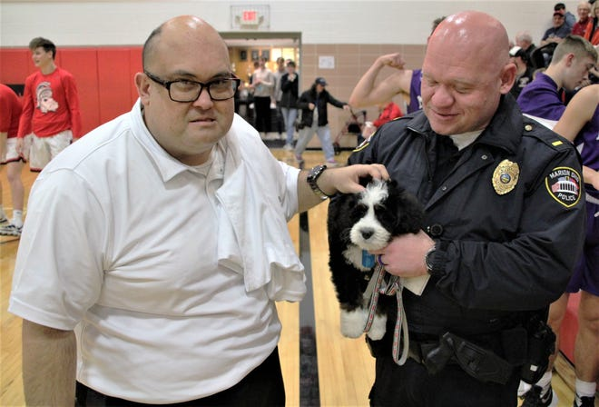 Marion resident Chip Amnathaphonthip, left, gives a pat on the head to K9 Chip, the newest member of the Marion Police Department K9 Unit. K9 Chip is named in honor of Amnathaphonthip, fulfilling a promise Marion Police Chief Bill Collins made to the local man two years ago. Lt. B.J. Gruber of MPD is holding K9 Chip.