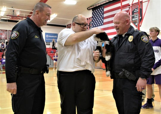 Marion Police Chief Bill Collins, left, and Lt. B.J. Gruber, head of the MPD MPACT program, right, watch as local resident Chip Amnathaphonthip plays with K9 Chip, a Bernedoodle puppy that is being trained as an emotional support dog for the department's K9 Unit and MPACT program. Collins announced Tuesday prior to a Pleasant High School boys basketball game that the puppy is named in honor of Amnathaphonthip.