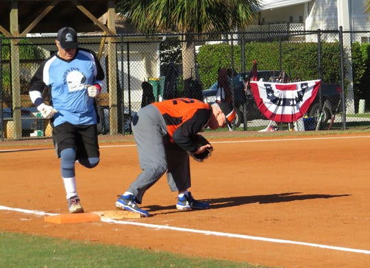 Sand Bar's first baseman Steve Clark scoops the ball out of the dirty getting the put out on Snook Inn's Tom Loiacono.