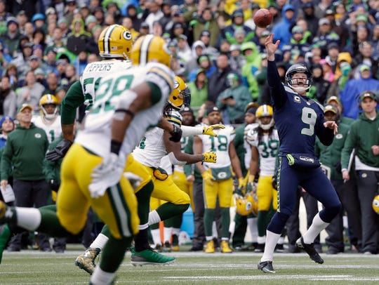 Seattle Seahawks' Jon Ryan (9) throws a touchdown pass on a fake field goal attempt during the second half of the NFL football NFC Championship game against the Green Bay Packers Sunday, Jan. 18, 2015, in Seattle.