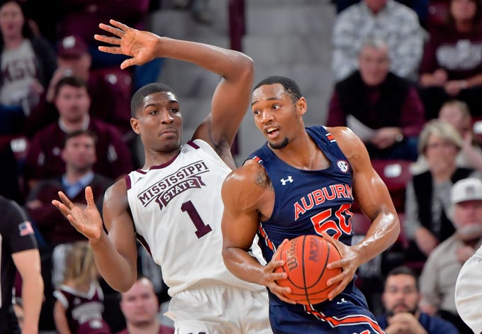 Jan 4, 2020; Starkville, Mississippi, USA; Auburn Tigers center Austin Wiley (50) looks to pass against Mississippi State Bulldogs forward Reggie Perry (1) during the second half at Humphrey Coliseum. Auburn won 80-68. Mandatory Credit: Jim Brown-USA TODAY Sports
