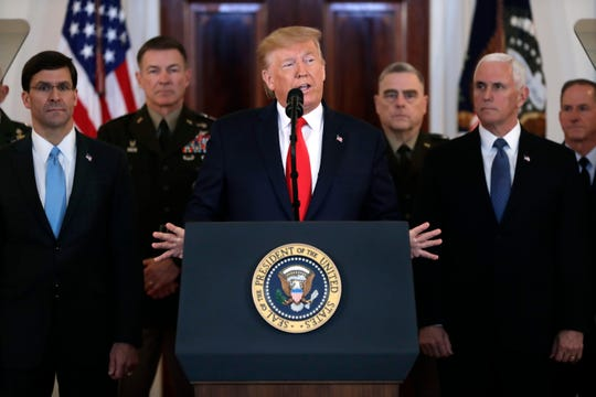 President Donald Trump addresses the nation from the White House on the ballistic missile strike that Iran launched against Iraqi air bases housing U.S. troops, Wednesday, Jan. 8, 2020, in Washington, as Vice President Mike Pence and others looks on. (AP Photo/ Evan Vucci)
