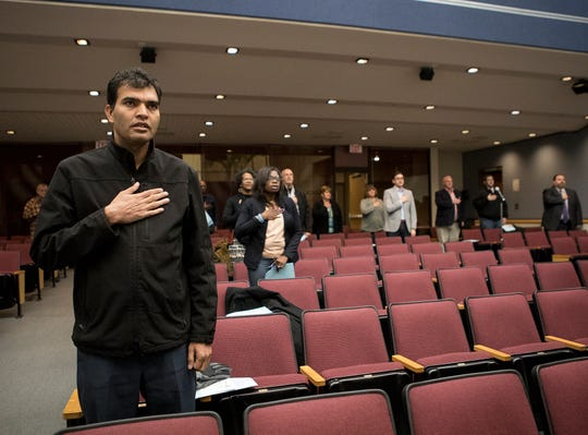 Bhuwan Pyakurel stands with his hand on his heart as he sits in on a Reyonoldsburg City Council meeting just days after being elected. Pyakurel made history as the first Nepali-Bhutanese person elected to any office in the United States.