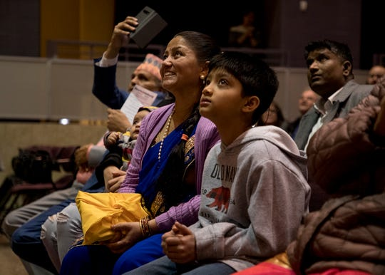 Dil Pyakurel and her son, Dev, look up at a screen showing Ohio Senator Sherrod Brown congratulating her husband, Bhuwan, for being the first Nepali-Bhutanese elected to office in the United States. Bhuwan was elected in November to Reynoldsburg City Council and was sworn in after Christmas.