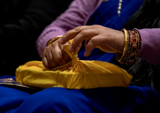 Dil Pyakurel, Bhuwan's wife carefully wraps up their copy of the Bhagavad Gita in cloth after her husband was sworn in to the Reynoldsburg City Council. The couple came to America as Bhutanese refugees with only a few dollars in their pockets. Bhuwan is now proud to say that he has a family, a job, owns his home and car and is now considered the first Nepali-Bhutanese elected to office in the United States.