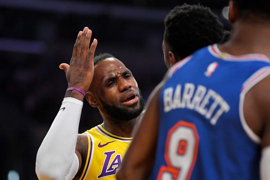 Los Angeles Lakers forward LeBron James, left, has words with New York Knicks forward Bobby Portis, center, as Knicks guard RJ Barrett listens after Potris hit Lakers guard Kentavious Caldwell-Pope in the head as he was shooting during the first half of an NBA basketball game Tuesday, Jan. 7, 2020, in Los Angeles. Portis was ejected.