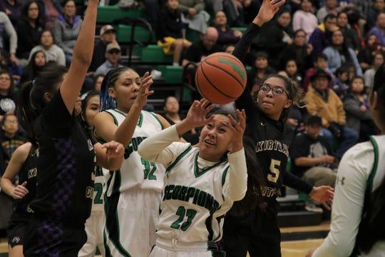 Farmington's Kiiyani Anitielu (23) looks to regain control of the ball against Kirtland Central during Tuesday's girls basketball game at Scorpion Arena in Farmington.