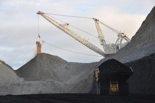 A coal hauler and a dragline operate at the Spring Creek Mine in Big Horn County in Montana.