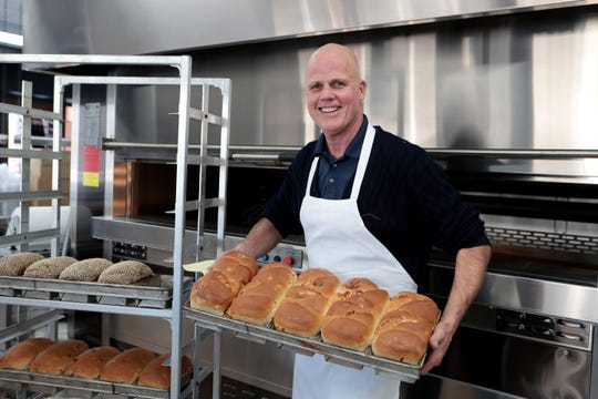Aspen Mills Bakery owner Marty Webster holds some freshly baked breads inside the bakery in Palm Springs, Calif., on Tuesday, January 7, 2020.