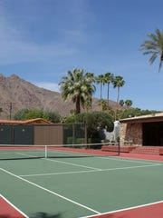 A full tennis court fills the back of the property. Behind the lot, at left, is the Dinah Shore House.