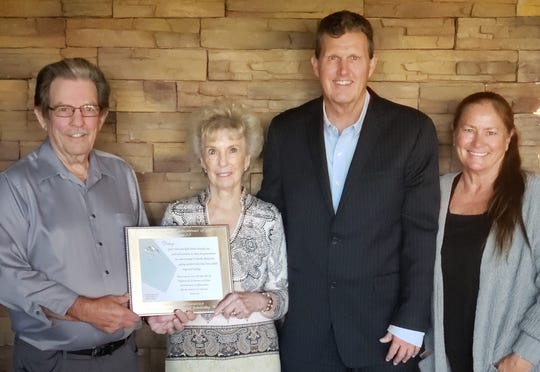Dave Shader and Daisy Catchings-Shader hold the Danny Catchings Memorial Scholarship Fund Award; with them are Pastor Dave Page and his wife, Carrie.