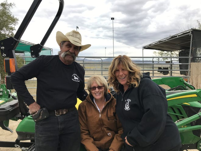 Cindy Currie poses on the ranch with Dave DiMeno, the Rescue president, and Annette Garcia, the Rescue director.