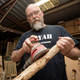 Oscar Morris works on sanding down a Christmas tree to make a cane at his woodshop in Eustis.