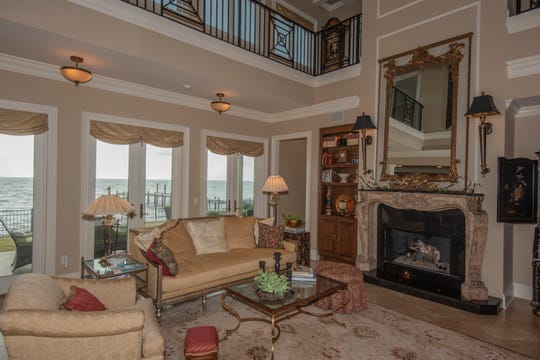 The living area with an elegant fireplace overlooks the waterfront.