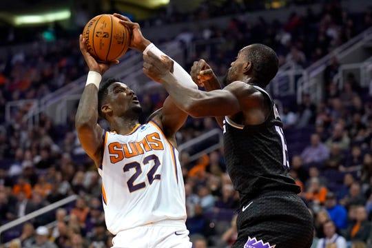 Phoenix Suns center Deandre Ayton (22) shoots over Sacramento Kings center Dewayne Dedmon during the second half of an NBA basketball game Tuesday, Jan. 7, 2020, in Phoenix. The Kings won 114-103. (AP Photo/Rick Scuteri)