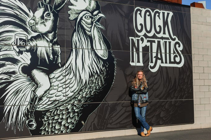 Arizona native and LA guitarist Kurt Johnson stands in front of the large mural decorating his new uptown bar and restaurant, Cock N' Tails.