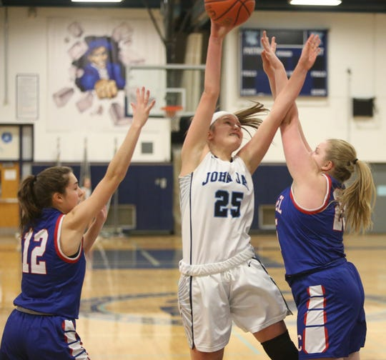 John Jay's Gabrielle Sweeney goes for a layup between, from left, Carmel's Kristina Leonard and Lilly Alexander during Tuesday's game on January 7, 2019.
