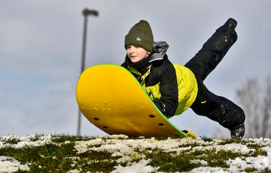 Jonathan Bluett, 10, leaps onto his sled for a run down the hill at Springettsbury Township Park, Wednesday, January 8, 2020.