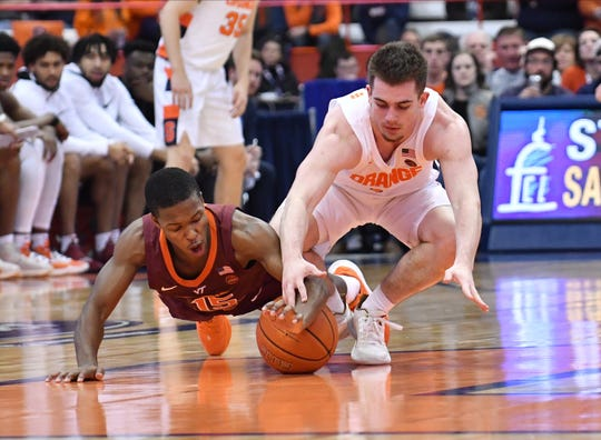 Virginia Tech Hokies guard Jalen Cone (15) and Syracuse Orange guard Joseph Girard III (11) battle for a loose ball in the first half at the Carrier Dome.