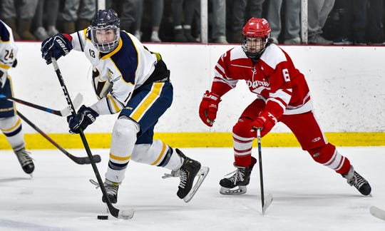 Victor's Jack McCandless, left, clears the puck away from Penfield's Cole Patton during a regular season game at the Rochester Ice Center earlier this month. McCandless leads the Blue Devils with 12 goals this season.