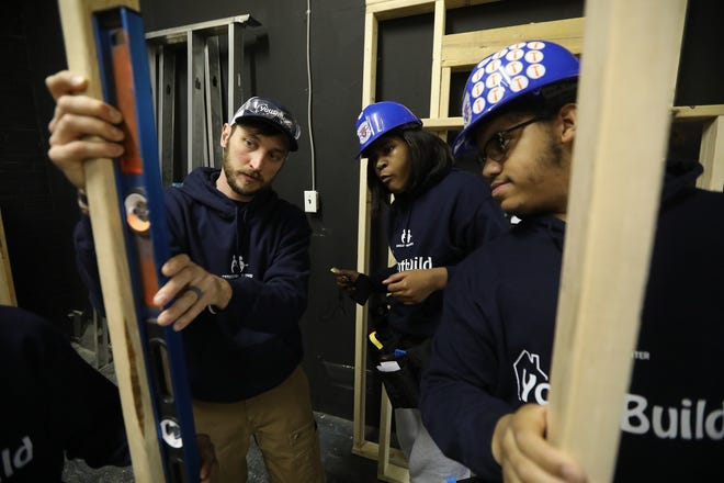 Nick Brown, construction skills instructor, tells students Callesyah Duggans and Bobby Archetko, right, why he is checking the frame with a level. The Catholic Family Center YouthBuild program helps students learn construction skills and assists those who want to earn a general-equivalence degree. YouthBuild is located on Lincoln Ave. in Rochester.