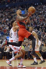 Portland Trail Blazers guard Damian Lillard (0) drives to the basket and is fouled by Toronto Raptors guard Patrick McCaw, let, during the second half of an NBA basketball game Tuesday, Jan. 7, 2020, in Toronto.