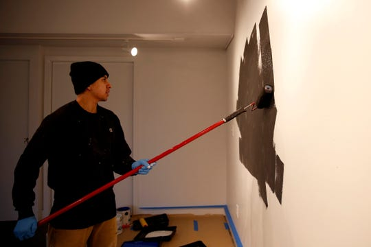 """Eddie Caine paints a background for an installation at the Salem Art Association on Jan. 8, 2020. Former Marines Matthew Boulay and Eddie Caine are pairing up to create """"Yellow Squares Bombed"""", to combine their fine art and graffiti art styles. The exhibit runs through Feb. 20."""