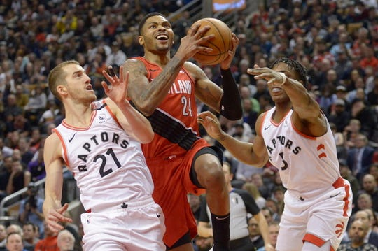 Portland Trail Blazers guard Kent Bazemore (24) drives to the basket against Toronto Raptors guard Matt Thomas (21) and forward OG Anunoby (3) during the second half of an NBA basketball game Tuesday, Jan. 7, 2020, in Toronto.
