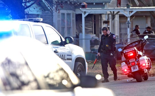 A police officer leaves the scene of a standoff that resulted in a suicidal suspect in custody on the 100 block of W. 11th Street on Wednesday, Jan. 8, 2020.
