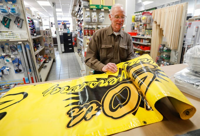 Jerry Sanders, owner of the National Art Shop, unrolls the 50th anniversary sign that he will display in his shop.
