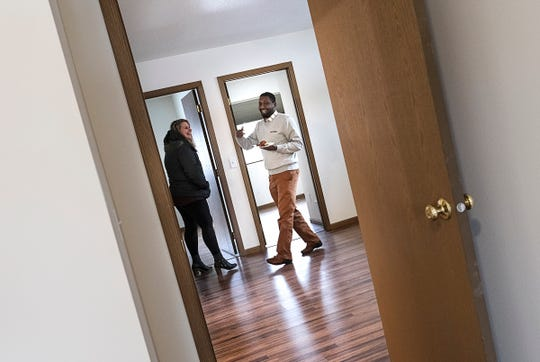 Ahmed Abdi smiles while showing visitors around his future home during a Central Minnesota Habitat for Humanity dedication Wednesday, Jan. 8, 2020, in St. Cloud.