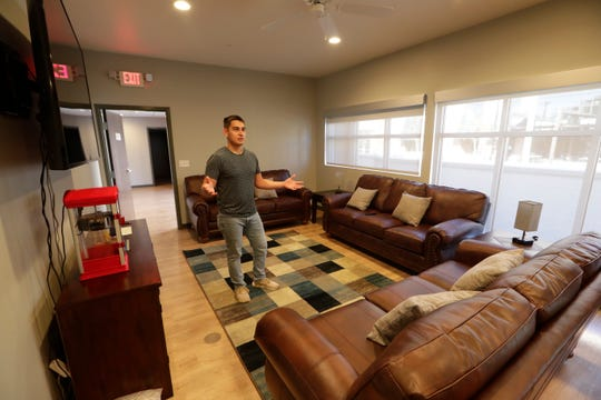 Roberto Vasquez, 19, house manager, gives a tour of the Bill and Nancy Malthouse scholarship house beginning in the gathering area where the housemates watch TV and hang out together.