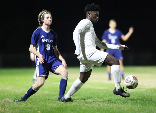 Florida High junior Delali Simpson tries to keep possession away from Maclay's Andrew Rentz as Maclay beat Florida High 3-1 on Jan. 7, 2019.