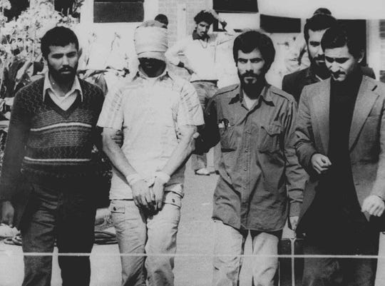 One of the American hostages, his hands bound and his eyes blinfolded, is displayed to the crowd outside the U.S. Embassy in Tehran, Nov. 9, 1979, by some of the militant Iranian students who seized the embassy. Robert Anders, then of Port Charlotte, was among those who escaped capture and was returned home after a daring rescue plot devised by the CIA.