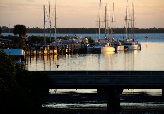 The sunrise is reflected on boats where Taylor Creek meets the Indian River Lagoon on Wednesday, Jan. 8, 2020, in Fort Pierce. St. Lucie County is planning to spend $3.5 million to dredge Taylor Creek to improve navigation at several marinas.