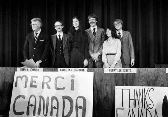 "A Canadian maple leaf dots the ""i"" in the French world for ""thanks"" as the six American diplomatic employees face the press at the State Department in Washington, Feb. 1, 1980. From left: Robert Anders, Joseph Stafford, Kathleen Stafford, Henry L. Schatz, Cora Amburn Lijek and Mark Lijek. The Canadians helped get the group out of Teheran."