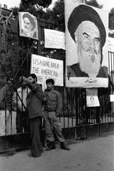 """USA, Give Back the American Shah Soon"" proclaims a poster next to a portrait of Iranian leader Ayatollah Khomeini on the gates of the American Embassy in Tehran on Nov. 8, 1979. While militants seized 52 American and held them hostage for 444 days, Robert Anders, then of Port Charlotte, was one of six who escaped and returned home after three months in hiding."
