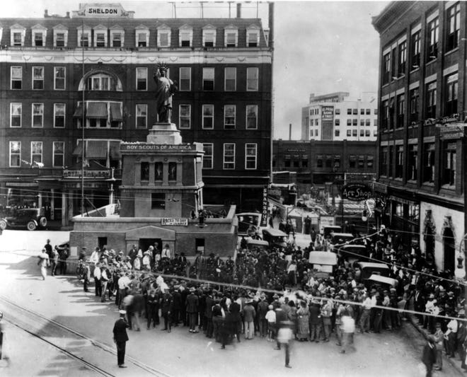"""Summer 1920: """"Liberty Statue,"""" which was dedicated in September 1918 and later given to the Boy Scouts after World War I. In the photo, a Mexican band plays, possibly Rayo Reyes, and construction is underway on the First Mortgage Building on Oregon Street and Sheldon Alley. At right is the Blumenthal building."""