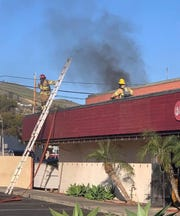 Fire crews battle a blaze on the rooftop of Kibo Sushi in Ventura.