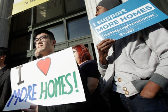 In this Tuesday photo, men hold up signs at a rally on the housing crisis outside City Hall in Oakland. California's Gov. Gavin Newsom said he is seeking $750 million to help pay rent for people facing homelessness, among other purposes, in the most populous state's latest attempt to fight what he called a national crisis.