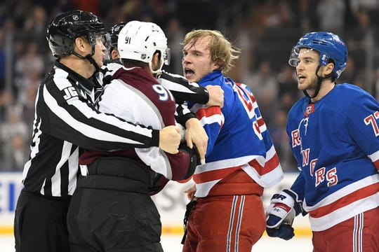 Jan 7, 2020; New York, New York, USA; Colorado Avalanche center Nazem Kadri (91) and New York Rangers defenseman Ryan Lindgren (55) are restrained by referees after fighting during the first period at Madison Square Garden.