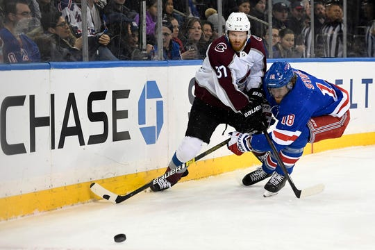 Jan 7, 2020; New York, New York, USA; Colorado Avalanche left wing J.T. Compher (37) battles New York Rangers defenseman Marc Staal (18) for the puck during the first period at Madison Square Garden.