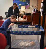 Ann Arnold-Ogden checks on her baby, Louis, while meeting with her boss, Margie Reese, at the Wichita Falls Alliance for Arts and Culture. Reese encouraged Arnold-Ogden to bring her baby with her during the work day.