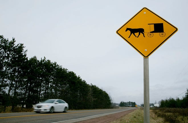 A horse and buggy warning sign is seen on Highway 186 in the town of Arpin. A proposed law would require horse-drawn vehicles to pay a registration fee to operate on the roadway.